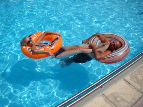 Eelke en Jon dobberen in het zwembad op twee grote luchtbanden