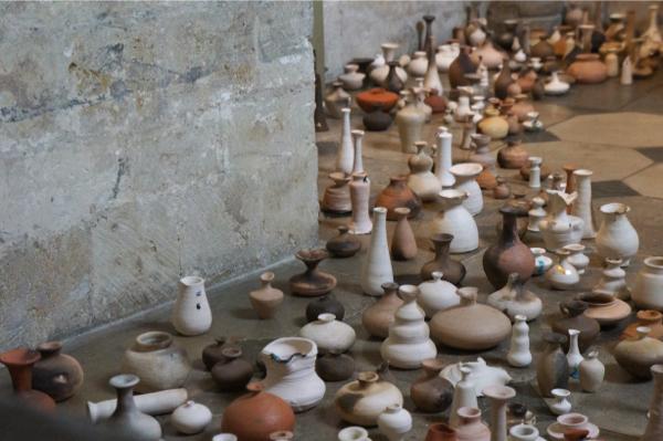 Verschillende keramieke flesjes op een  oude kerkvloer